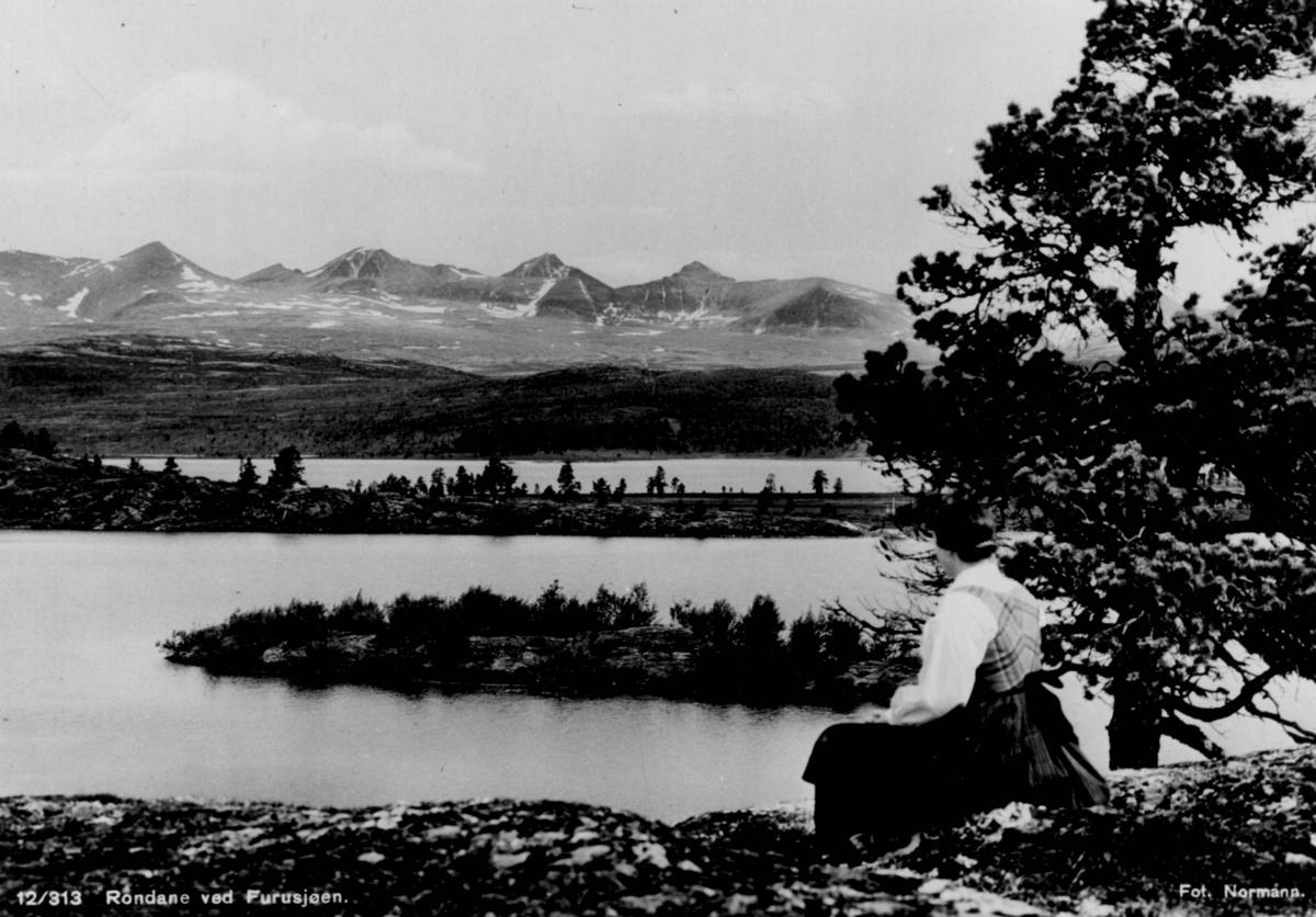 Avfotografert postkort. En kvinne i rondastakk som ser utover Furusjøen ved Rondane.