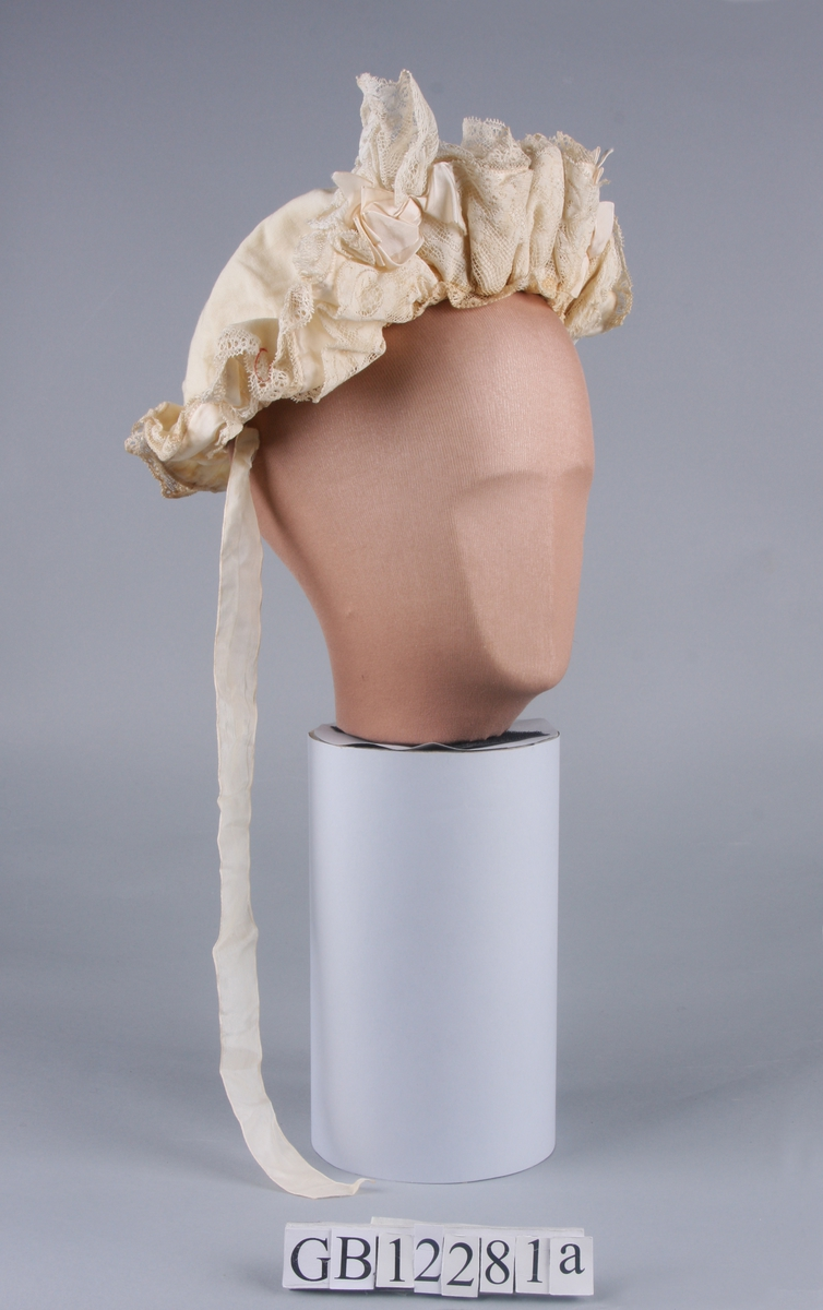 Rynket. Oppbrettet kappe med rynkete blonder. 3 rosetter. Knytebånd og trekkebånd.