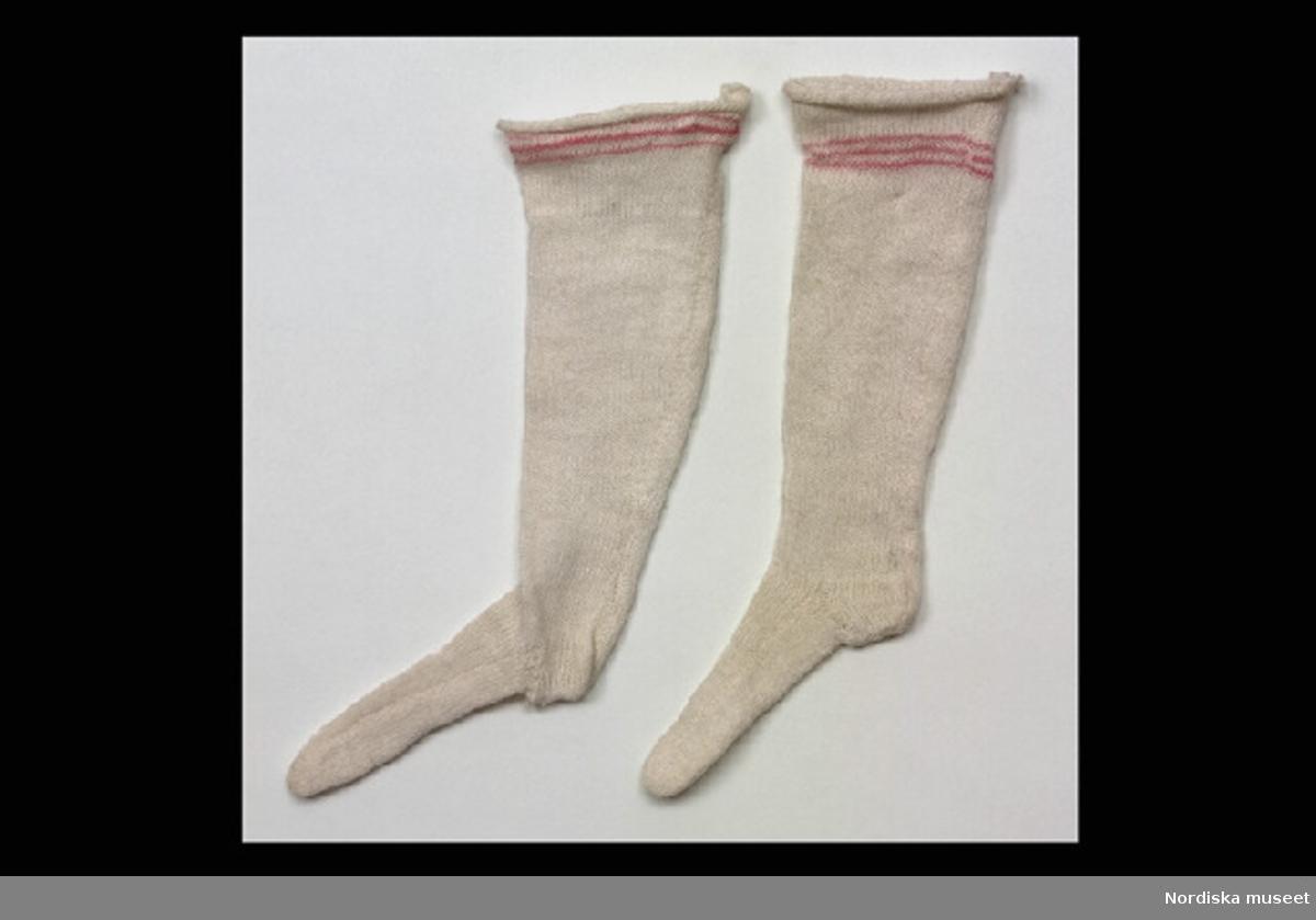 Inventering Sesam 1996-1999: L 11  cm Strumpor, ett par, till docka, stickade av tunt bomullsgarn, vita med röd rand i resåren.  Tillhör docka 108.265 och 108.266. Birgitta Martinius 1996