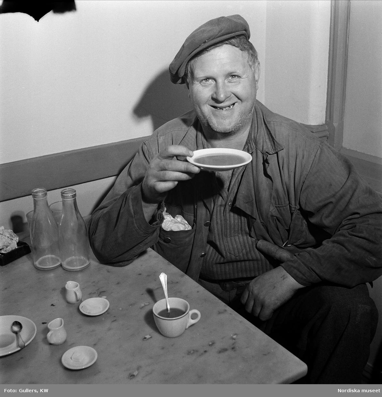 Man med keps dricker kaffe på fat, Göteborg.