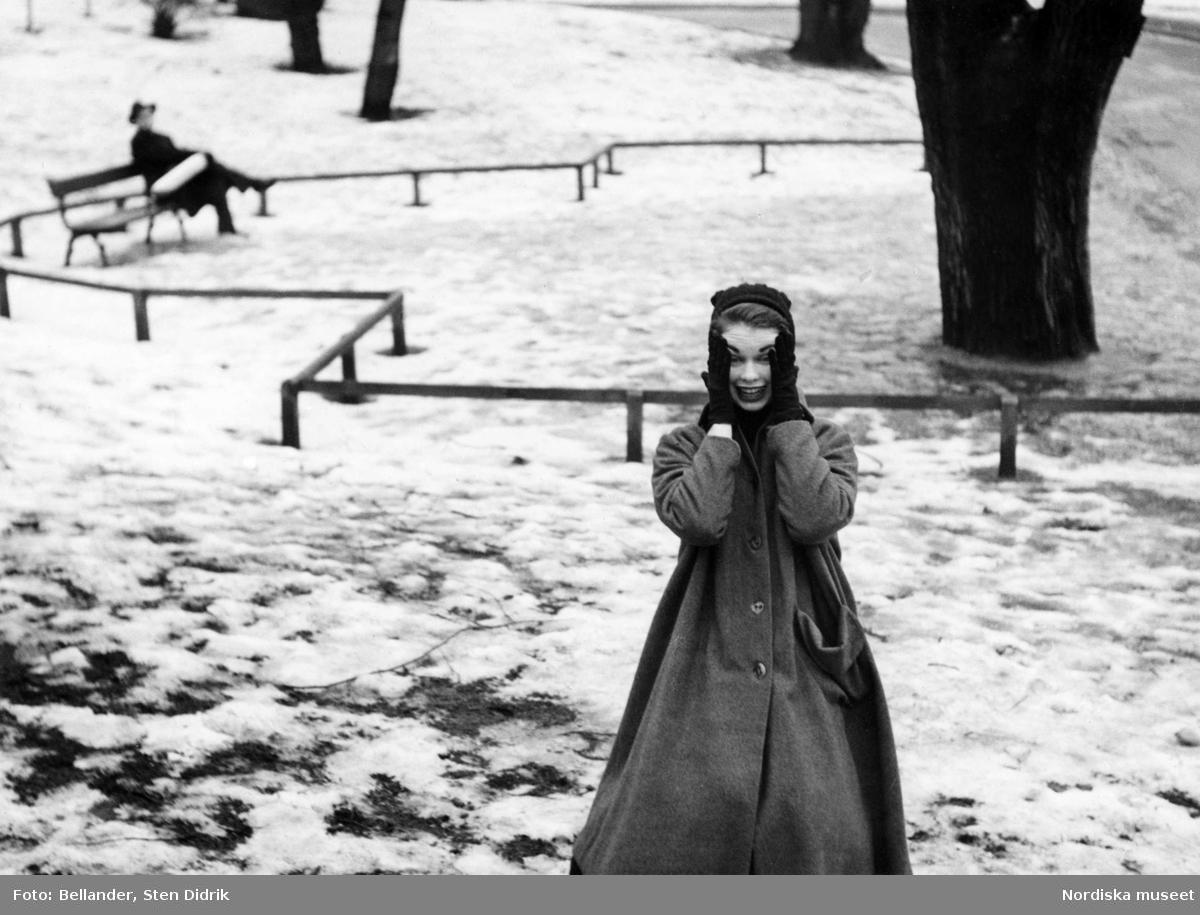 Vinter. Modebild. Kvinnlig modell trycker händerna mot kinderna. Hon står i en park med snö. I bakgrunden sitter en man med hatt och rock på en bänk. Stockholm.