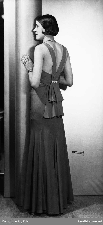Konfektion. Modell i hellång aftonklänning med dekoration och volanger i ryggen, lutar sig mot en pelare.