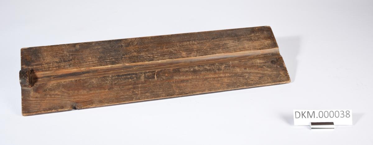 Avlang planke med en langsgående rille på midten. Rillen er åpen i den ene enden og stengt i den andre enden.