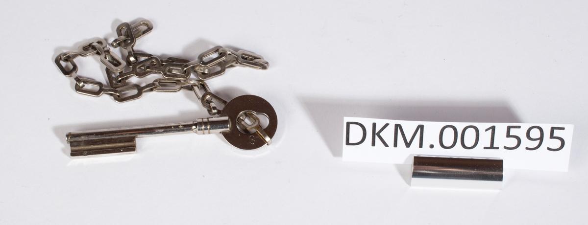 En nøkkel i en kjetting, den har trolig hørt til ett større knippe.