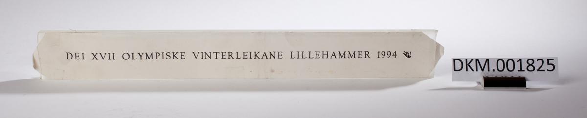 En rektangulær skive med inngravert tekst på den ene siden.