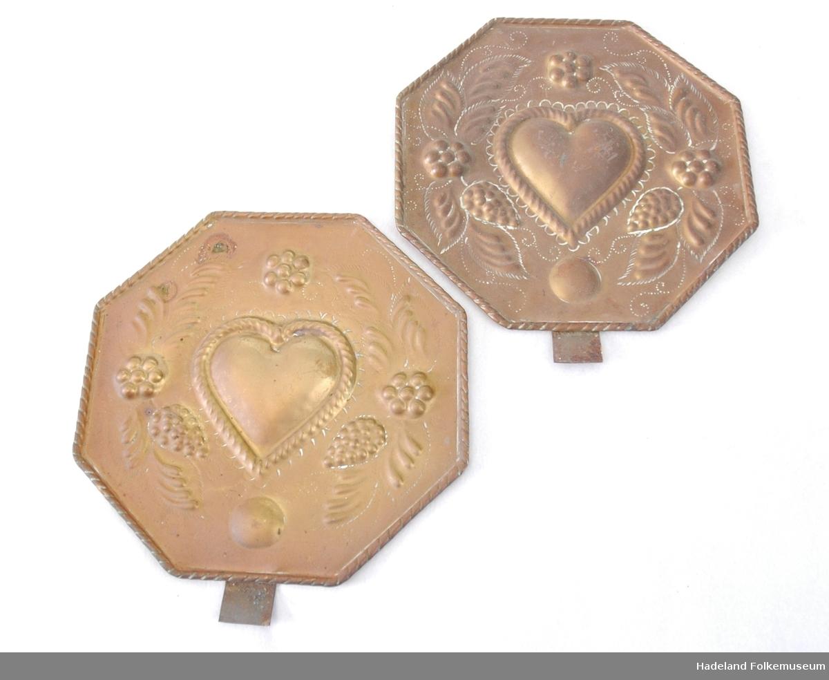 2 lysskjold. 8-kantet med dekor i relieff: hjerte, blomster og blader. Mangler kopp til plassering av lys
