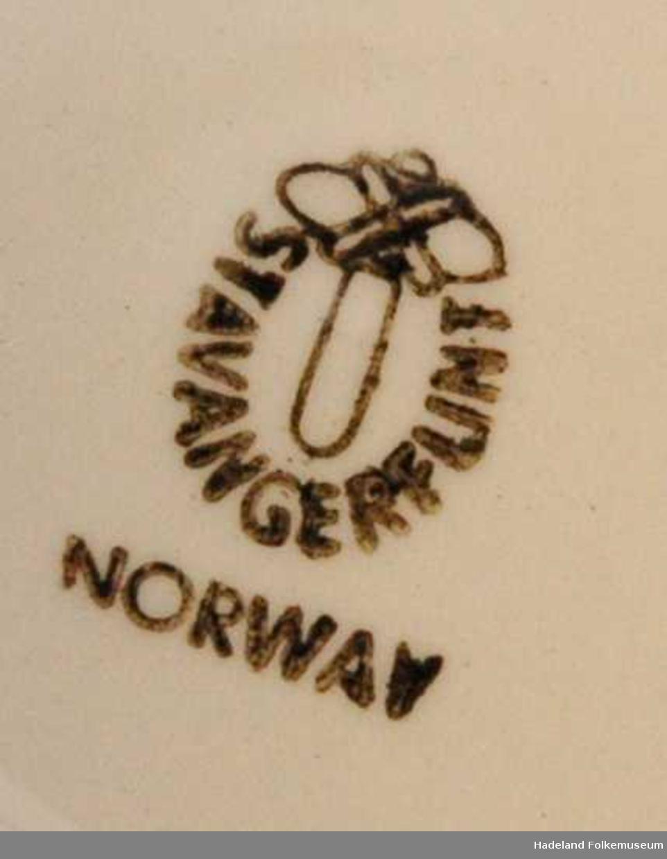 Monogram formet av en M og en B plassert i sentum av en bladkrans.
