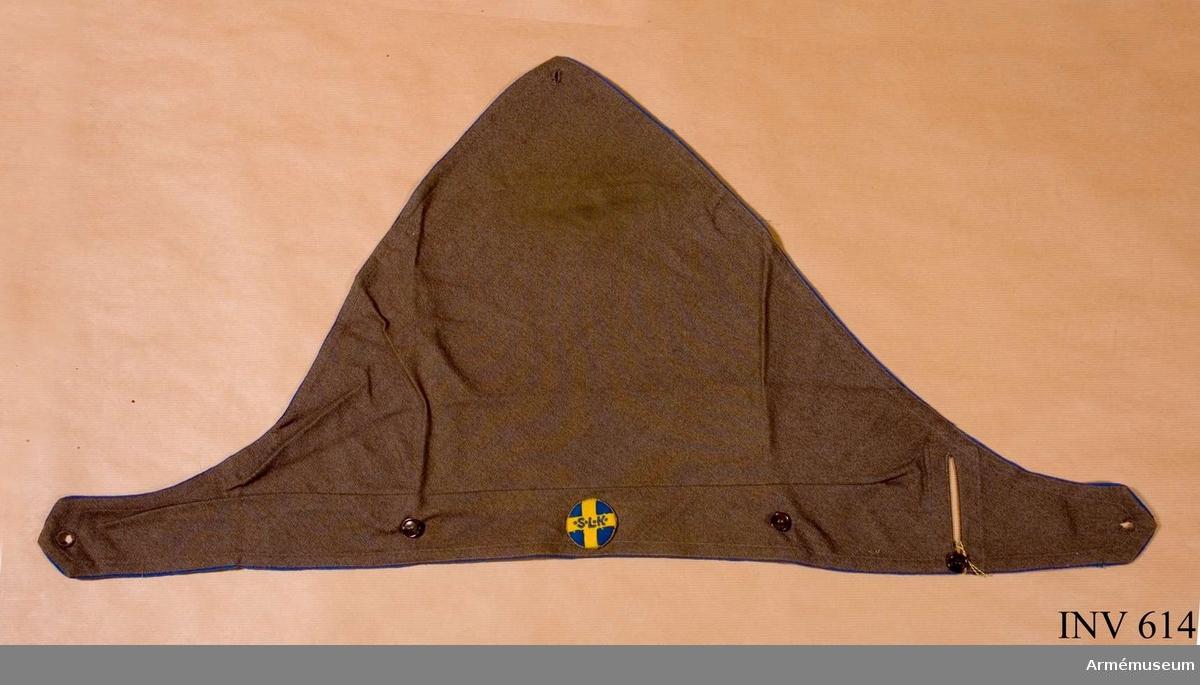 """Till kappa av grå bomull med 10 mm maskinsydda sömmar, passpoilerad med blått bomullstyg runt hela snibben. Ett knapphål i varje hörn. Tre st på framsidan, därav två vi pannan och ett mitt bak, 80 mm högt, rakt under instickshålet. Häri skall den högra snibbdelen stickas igenom. Mitt fram Sveriges Lottakårers märke i blått kläde med gult kors i kläde broderat """"S L K"""" i blått silke. Snodd av tvinnad guldtråd runt märket. Ägarinnan har tråcklat ett insyningsveck tvärs över snibben 50 mm från kanten, troligen för att få den mera klädsam. Mått: 770x550x50 mm."""