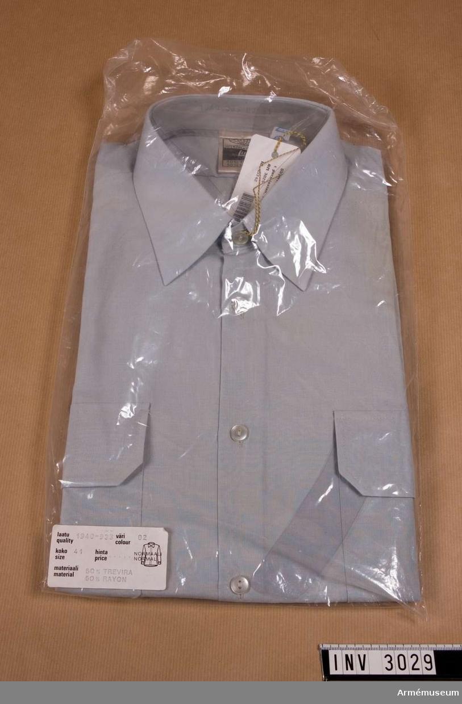 """Skjorta m/1958, manskap/userg f permission.Stl 41. Av 50 % Trevira och 50 % rayon (en i skjortor vanlig blandning, torkar fort, behöver inte strykas). Knäppt fram med vita pärlemorknappar. Två bröstfickor med lock, knäppta med vita pärlemorknappar. Snedställda insticksfickor på framstyckena. Etikett i nacken """"International Lutha"""" och """"tvätt 60 gr."""" Tryckt på kragens insida """"1940 933 02 41"""". Avknäppbara axelklaffar med gradbeteckning två vinklar= undersergeant. Användes till permissionsuniform m/1965."""