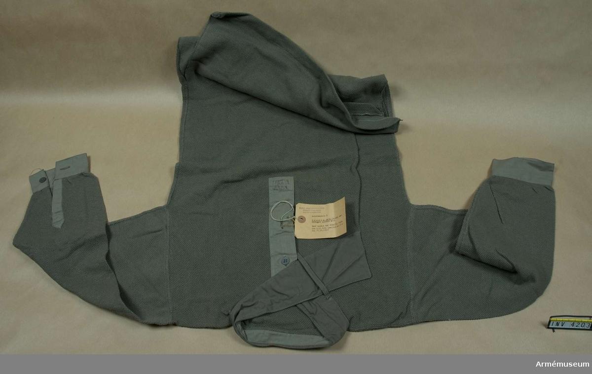 """Stl 5. Av gråbrungrön kypertstickad trikåväv. I nacken vid halslinningen en förstärkning av samma tyg. Vid halslinningen är halsduk m/1939 fastsydd, fastställd 1941-04-04. Tillv. då av gråbrungrön bomullssatin, här av domestik, att bäras t fältuniform m/1939 när vapenrocken bars högknäppt. Bredd i nacken: 35 mm, stb ytterändar: 100 mm, 750 mm lång. Ena ändens insida har snedgående hälla var igenom den andra änden dras f att hålla halsduken på plats. Kallad """"idiotslips""""; tydligen ej populär. Den blev inte mera omtyckt när den syddes fast vid skjortan. Bestämmelsen upphävdes dock efter någon tid. Tillv. i tre storlekar m storleksbeteckningar 4, 5 och 6. Märkt m vävd etikett """"5"""" framtill H insida. Vidhängande etikett anger fastställelsedag: """"Kungl Arméförvaltningen, Intendenturavdelningen, Utrustningsbyrån. Arbetsmodell å Skjorta m/39 (trikå) med fastsydd halsduk m/39. KAFI beslut dnr 4860/51 UtrB,den 1.11.1951 (ast/utr nr 57:2 den 29.10.1951""""."""