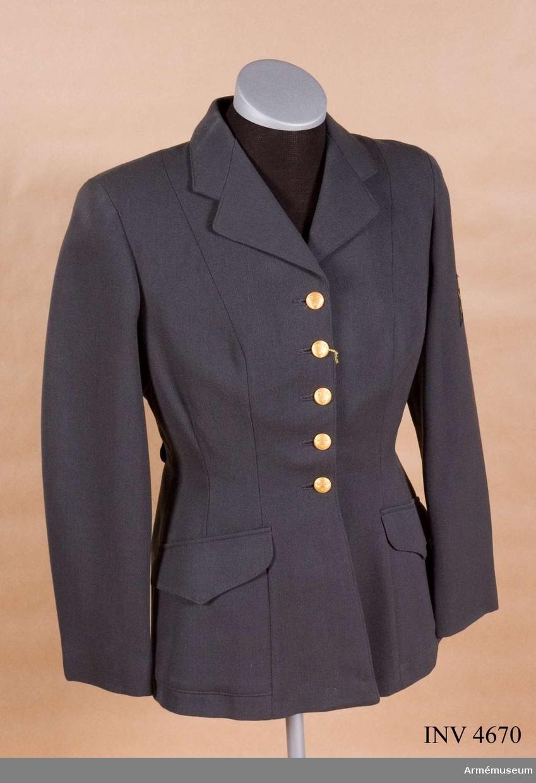 """Stl 40. Modellen tillverkades under åren 1960-1966 av stålgrå  yllediagonal, 100 % ull. Från år 1966 övergick man från yllediagonal till ripsdiagonal - 65 % ull och 35 % polyester -  vilken kvalitet visat sig i många avseenden bättre. Modellen bibehölls. Jackan är enradig, knäppt med fem medelstora 19 mm uniformknappar m/1939-1960 guldfärg. Den har enradiga slag, insvängd midja, två påstickade snedställda sidfickor med spetsfasonerade ficklock, lös ryggslejf knäppt på två  medelstora 19 mm uniformsknappar m/1939-1960 guldfärg. På  insidan av höger framstycke en innerficka. Jackan är helfodrad med svart konstsidenfoder, vilket vid senare tillverkning  utbyttes mot svart nylontrikåfoder. På vänster ärm 15 cm från  axelsömmen försvarsgrenstecken stort för armén i vävt  utförande. För officers och underofficers tjänsteklass är  tecknet utfört i guldbrodyr. Nytt tjänsteställningssystem  infördes att gälla från 19720701. Detta medförde ingen ändring  av anbringande eller utformning av tecknet men beskrivningen  erhöll följande lydelse: """"Försvarsgrenstecken för armén  tillverkas i guldbrodyr i stort format för förordnad  civilmilitär personal samt för civil personal av tjänstegrupp 1 - 3 och i vävt utförande i gul färg i stort och litet format för övrig personal"""". (Litet format på axelklaffhylsa på rockklänning m/1960.) Märkning: På ryggens insida på fodret under hängaren stämpel: Tre kronor 1963. Till höger därom vävd storleksetikett: 40. Under innerfickan vävd etikett: """"Te-Be-We kvalité"""", firmanamn för tillverkaren Thure B Wiberg, Malmö."""