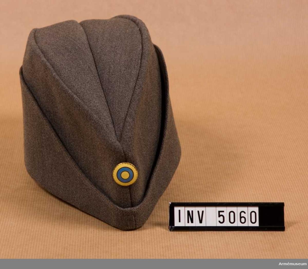 Tillverkad av gråbrungrön yllediagonalkläde i överensstämmelse med fältmössa m/1939 men något högre än denna. Uppslagen något annorlunda utformade och till skillnad mot färtmössans uppslag har denna två kantstickningar. Mössan är fodrad med ett grått foder och har svettrem av grå bomullstwills.Märkning: 56 ÖSB ( = Örebro Sport & Bil, 56 avser storlek)  Paris 8 .