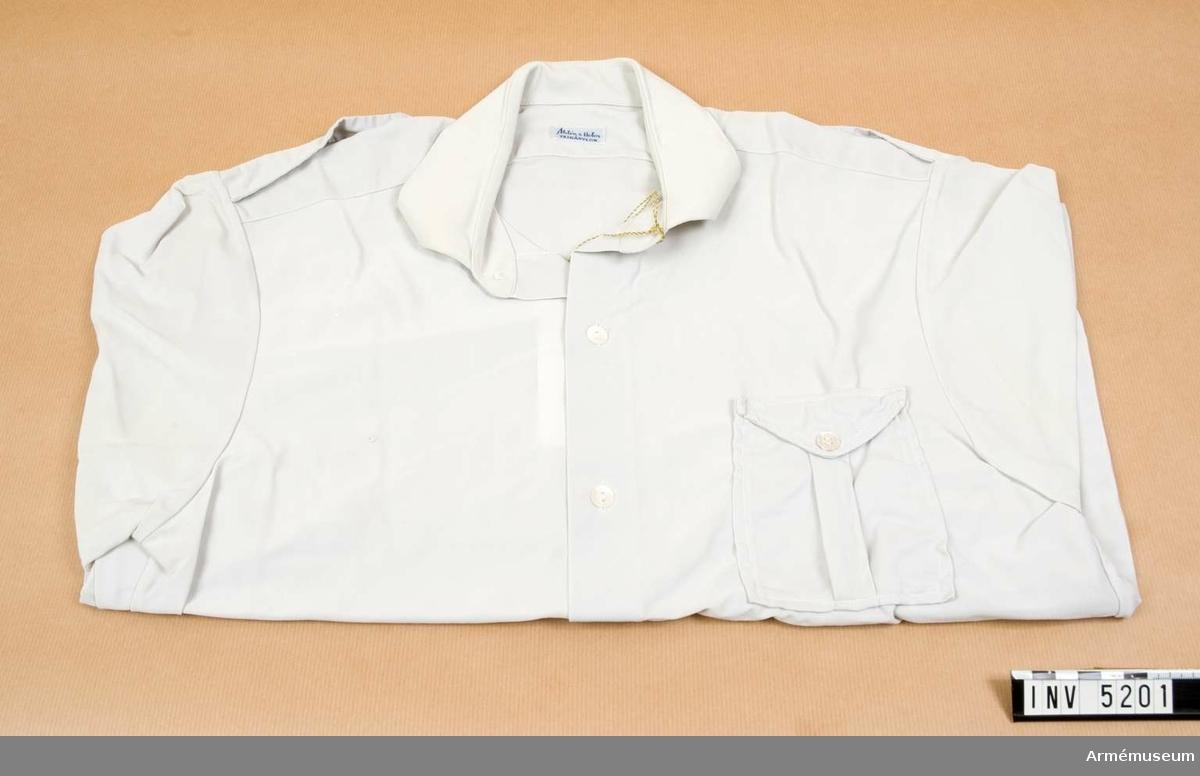 Skjorta t högtidsdräkt, grå, bilkårist.Tämligen gott skick. Storlek: 40. Halsknapp saknas.Skjorta till högtidsdräkt för kvinnlig bilkårist 1950. Av grå  nylontrikå, Åhlén & Holm. Förseddmed ok och fasta, smala axelklaffar knäppta vid halsen med liten blusknapp. Ficka på  vänster sida, med veck på mitten, ficklock, knäppt med blusknapp. Manschett, enkel, knäppt med en knapp. Knäppt  framtill med sex vita pärlemorknappar. Bäres till högtidsdräkt, Sveriges kvinnliga bilkårers förbund.