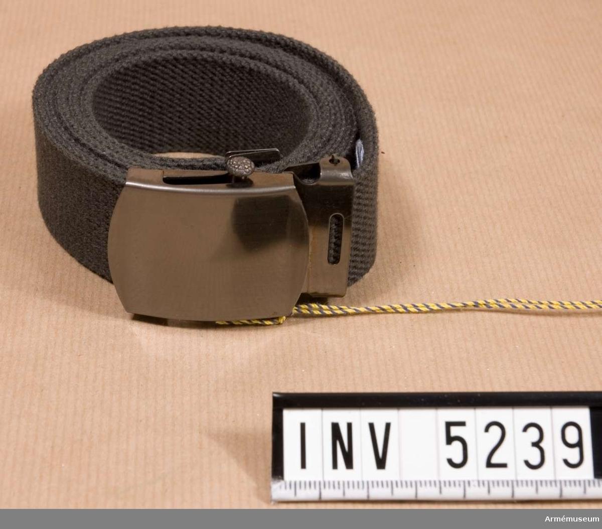 Textil. Längd: 1200 mm. Bredd: 30 mm.Tillverkat av stålgrått textilband med spänne av stål. Stålspännet märkt Sa Ve = Sam Vedin Stockholm.