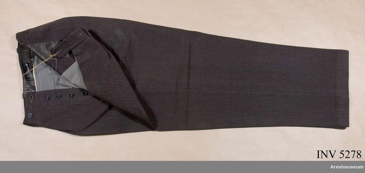 Storlek: B 100. Mörkt gråbrungröna byxor, mörkare än vapenrocken, tillverkade i yllediagonal. Jylfknäppta med hällor i linningen. Sidfickor ooh en bakficka. Daglig dräkt.