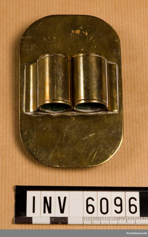 Av mässing med oval botten. På baksidan öglor avsedda att fästa i hål i trumremmen. På plåtens framsida, mitt på och tvärs över denna finns två runda hållare för trumpinnar; invändigt klädda m grön filt.  Samhörande nr är 5828-5899, 6000-6099, 6200-6212.