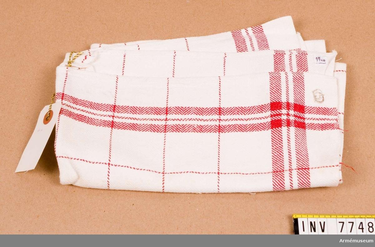 Handduk.Vit. Rutor 48 x 48 mm och två grövre och en finare linje, allt  i rött, runt om. Märkt med en krona.Ingår i fotomaterielsats 7 låda 1.
