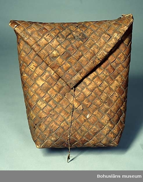 Kont av flätad björknäver, tillverkad i ett stycke. Rektangulär form, bredare upptill med ungefärligt bottenmått 38 x 22 cm.  Övervikt, snibbformat lock med sekundärt stängningssnöre att vira runt istucken täljd träbit på kontens framsida.  På baksidan bärremmar bestående av olika material;  vänster bärrem med fästanordning upptill av tvinnat tagel, fästad inuti mot täljd träbit, läderrem nertill av av barkgarvat läder och däremellan fästat näverflätad bred rem att bära över axeln; höger bärrem med fästanordning upptill av barkgarvad skinnrem, fästad inuti mot täljd träbit, undertill av råhudsrem fästad i flätad hampalina och däremellan fästad näverflätad bred rem att bära över axeln. Ursprungligen har bärremmarna troligen bestått av tagel, näver och råhud.  Kontens kanter är något trasiga. Smutsig, stel.  Ur Knut Adrian Anderssons katalog: No 105 Lapp-kont Väska gjord av Lappar att bära mat uti. Sk. 1868 av Löjtnant C. Vising i Uddevalla