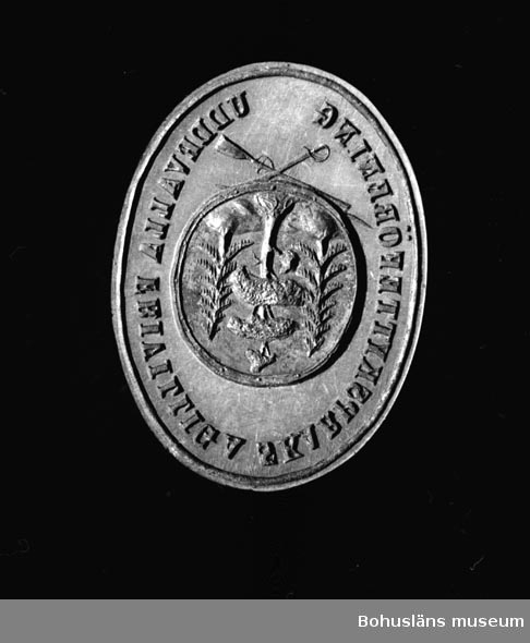 Ur handskrivna katalogen 1957-1958: Sigill, mässing Oval stamp, mått: 3,8 x 2,2 cm, av mässing. Uddevalla frivilliga skarpskytteföreningen. Svart skaft. Helt.  Lappkatalog: 36