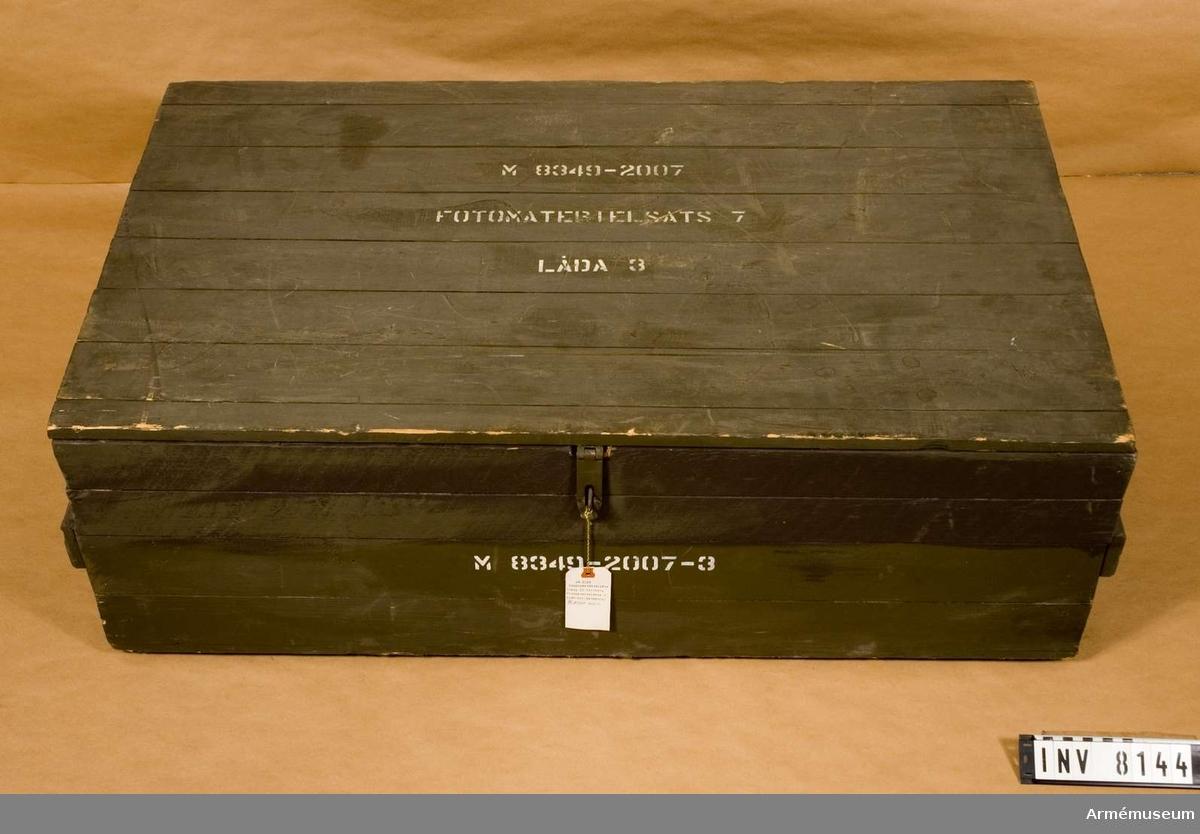 """Trälåda t fotomaterielsats 7. Låda 3.Låda av trä, målad grön utanpå. Gult trä inne i lådan.  Lock med gångjärn.  Märkt """"M8349-2007-3"""" på framsidan, locket och på högersidan. På locket dessutom """"Fotomaterielsats 7. Låda 3."""". Innehåller utrustning för fotomaterielsats 7 låda 3."""