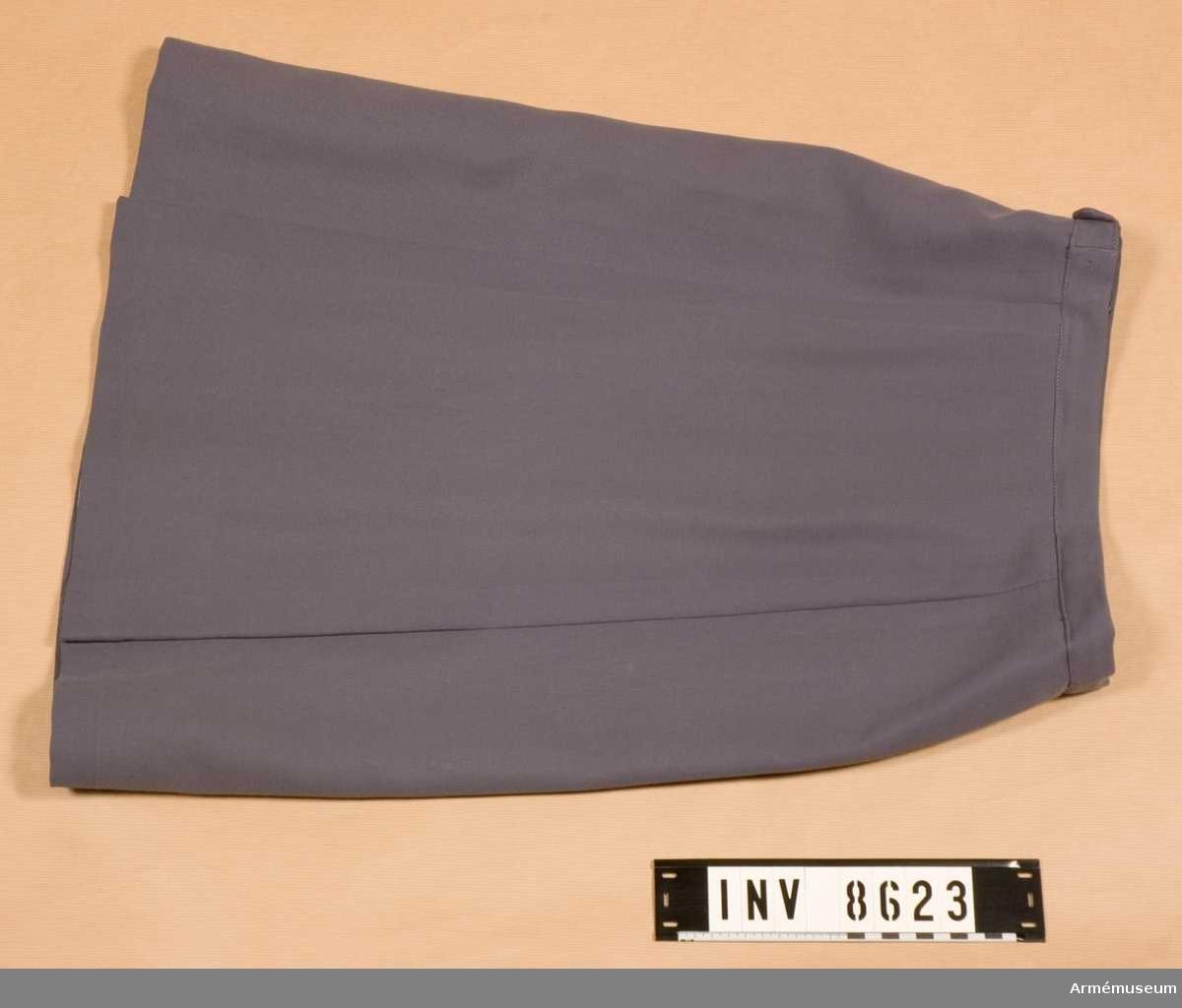 Samhörande gåva 8617-8626. En blågrå något utställd kjol med linning, blixtlås i vänster  sida och veck på var sida av den infällda framvåden. Kjolen är fodrad med grått siden. Den är både nedlagd och utsläppt i sömmarna bak vilket syns i de ursprungliga pressvecken. Hettermarks konfektionsfirma. Källa SLK Värt att veta... 1970 sid 18.