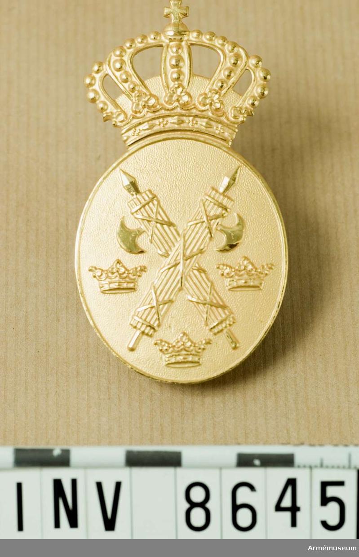 Vaktmärke av äldre modell, typ 1960.  Höjd 75 mm. Bredd 40 mm. Vikt 36,7 g. Ett ovalt märke i förgylld metall krönt med kunglig krona. Märket visar två korslagda spöknippen och tre öppna kronor. Frånsidan är märkt F 16 4 Sporrong Stockholm. Anbringas på vänster bröstficka. Källa UNIA 1960 14:2.