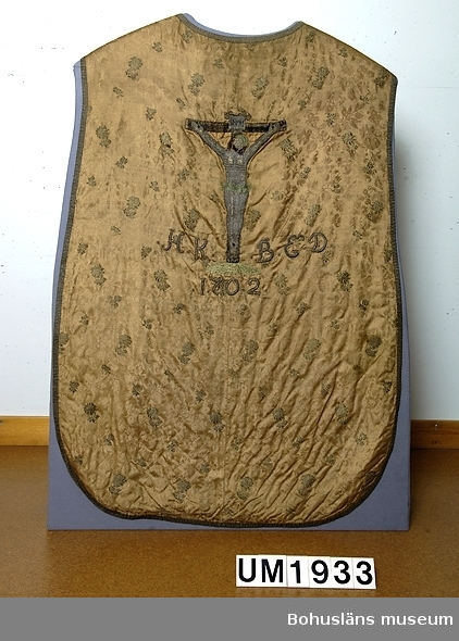 """Mässhake från Uddevalla kyrka i sidendamast, ursprungligen troligen ljust röd; invävt s.k. broscherat mönster (blommor) i förgylld metalltråd som numera svartnat.  Ryggsidan: Broderat krucifix; förgylld metalltråd och silke. Krucifixet i låg relief monterat på sidentyget.  Ur handskrivna katalogen 1957-1958: Mässhake, U-a kyrka H. 100 resp. 122 cm. Monterad å vitt tyg, insatt i glas och ram; ramen: 144,5 x 100cm. """"H.K:B:E.D. 1702""""  Lappkatalog: 12  1742 i (Norra Ryrs) Lane-Ryrs kyrkas inventarium. Mässhaken är omnämnd i Lane-Ryrs kyrkas """"Förteckning över lösa föremål av historiskt eller konstnärligt värde, som böra vara uppförda i kyrkans inventarieförteckning"""". Upprättad av Fil. kand. Hanna Eggertz i oktober 1919, under Föremål som förut tillhörigt Lane-Ryrs kyrka. Samtliga nu i Uddevalla museum."""