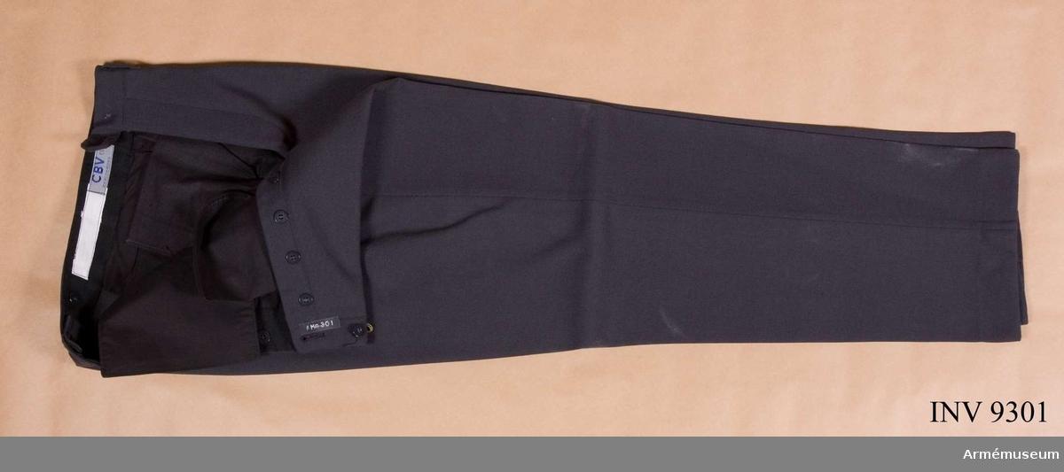 Av stålgrått ylletyg, baratea. Är jylfknäppta med knappar, har linning och saknar uppslag nedtill. Två sidfickor och två bakfickor med knäppsleif.Storlek C 50.