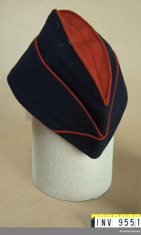 Båtmössa av fransk modell 1958.Av mörkblått kommisskläde. Har en röd passpoal runt brätterna och kullen (det invikta) är av rött kläde. Är märkt på det mörkblå bomullsbandet (svettremmen) UGECO 57.