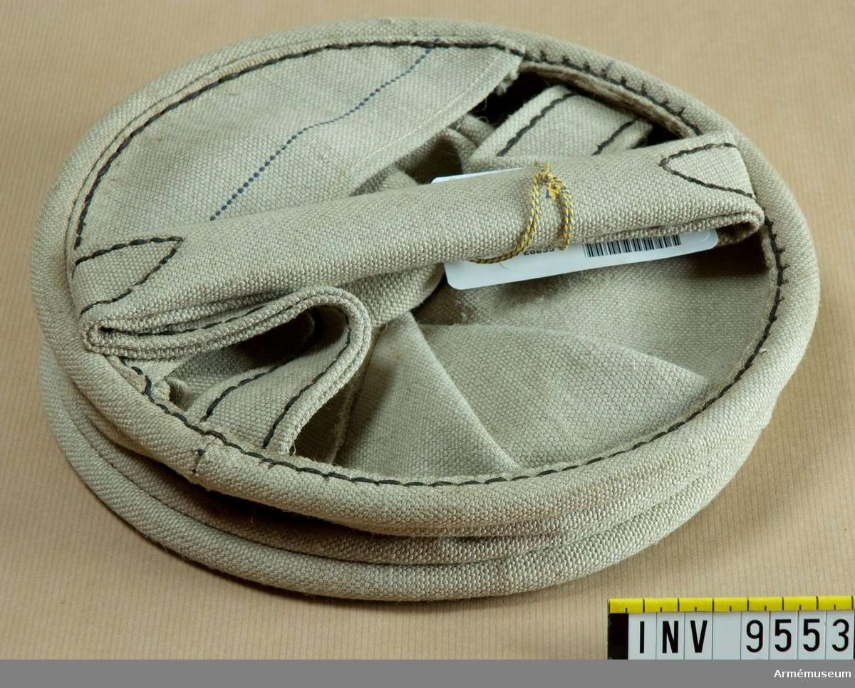 Av oblekt bomullstyg med hållande ringar upptill och nedtill. Försedd med pip och handtag. Gåva från FMV.