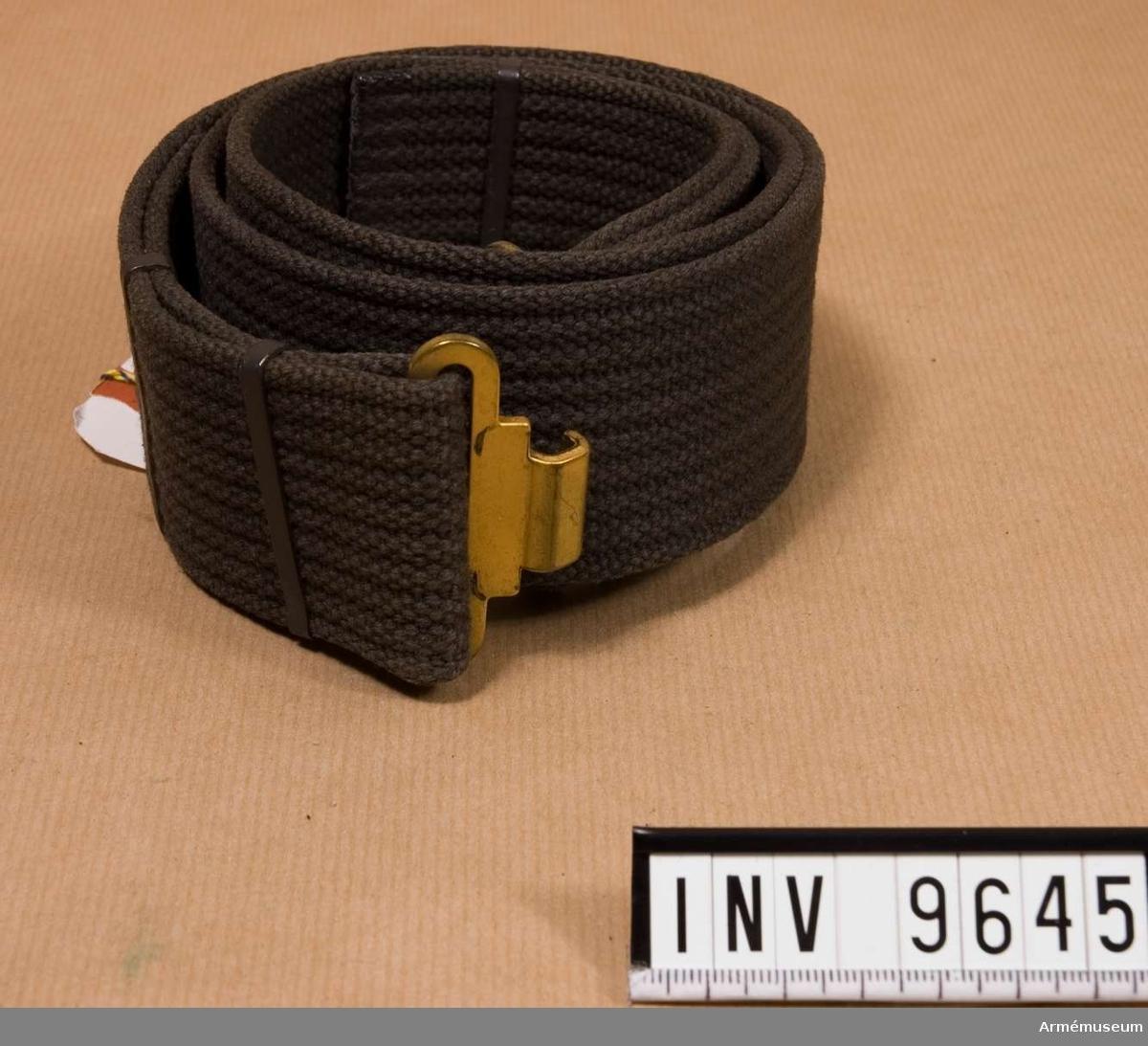 Samhörande nr i gåvan är 9605-9650 + 9659-9666. Av stålgrått bomullscord. Har ett gult, spänne i metall av  hyska och hake. Bärs utanpå dräkten. Numera ingår livremen i stridsselen.