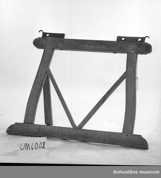 Ur handskrivna katalogen 1957-1958: Träställning med två järnstativ H.: 89 cm. (Järnstativen oräkn.) Basens l.: 1,24 m. Föremålet rostigt. Helt.  Lappkatalog: 51