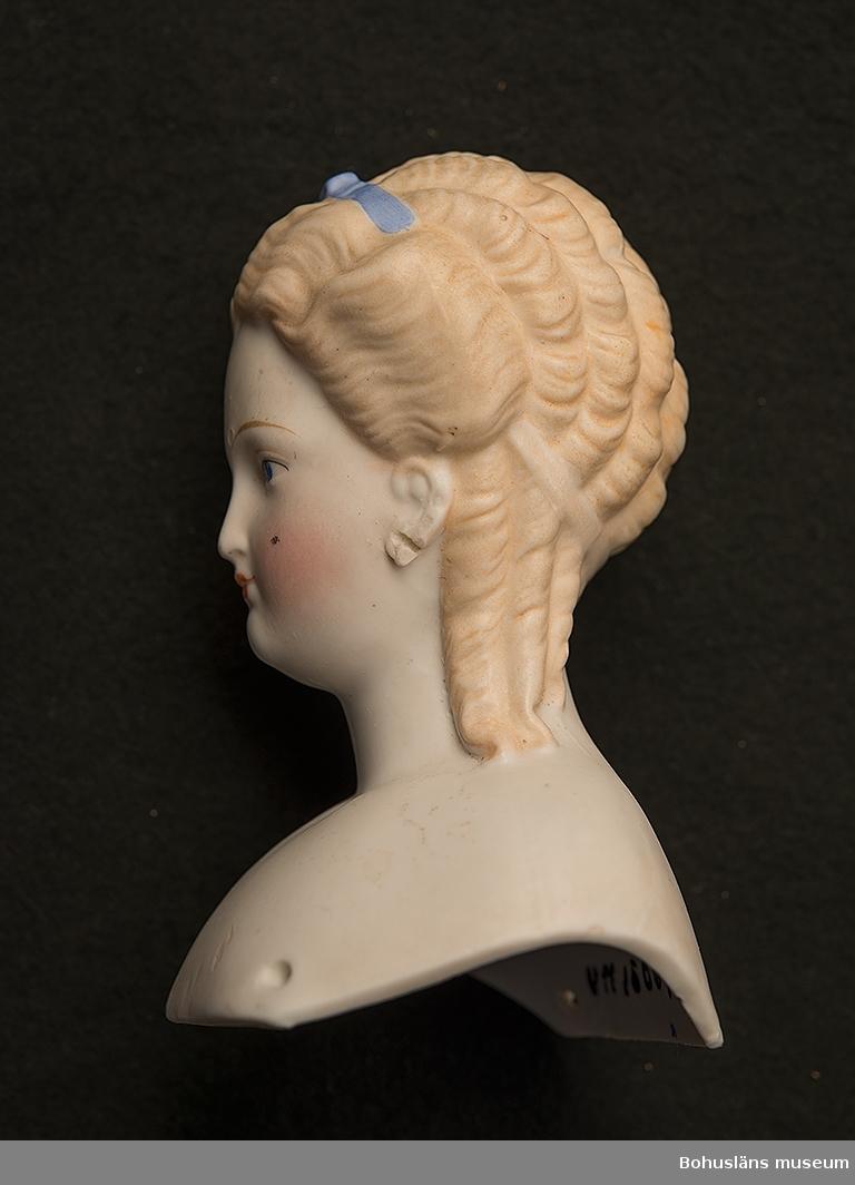 Dockhuvud av bysttyp. Hårfärg ljusbrunt med blått hårband. Håret mittbenat, vågigt. Ögon blå. Rosiga kinder. Öron målade. Vänster öra sönderslitet.  Förmedlare; se UM15009:001.