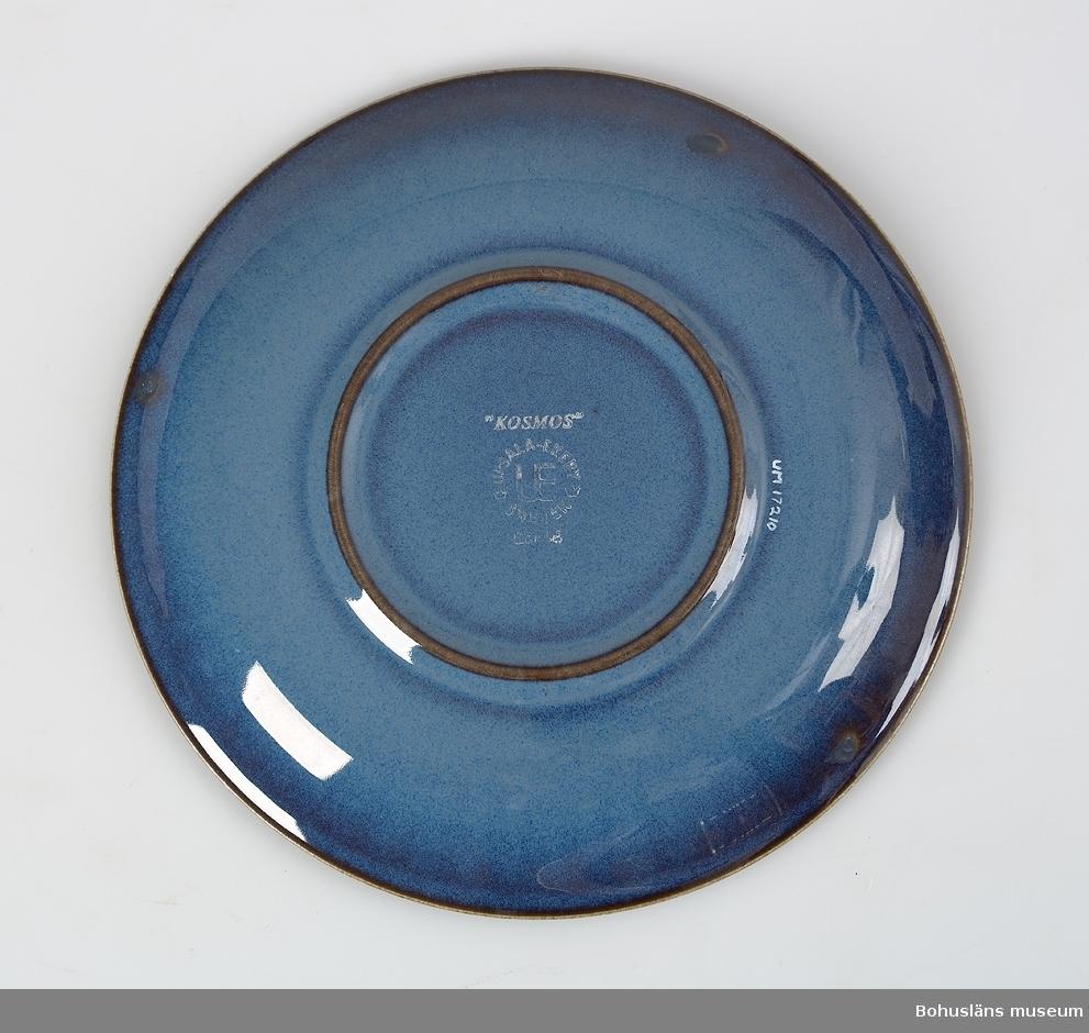 """Blå glasyr med brun underton, inpressad krans av tvärstreck runt fatets  kant och på koppen""""UPPSALA-EKERBY SWEDEN UE GEFLE."""" Del av teservis UM017208-UM017214."""