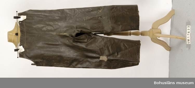 410 Mått/Vikt ! BENVIDD 33 CM Hängslebyxor att dra över annan klädsel som skydd mot väta. Gröna.     Går upp över bröst och rygg. I överkanten är det knappar att fästa     hängslen i. På knapparna står det Grundéns.                            Tre knappar saknas. Hängslen saknas. Slitna.                            Ingår i redskapsbestånd ur sjöbod från Hällsö, Havstenssund, Tanum sn. Se UM17521.
