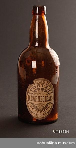 """Bred, cylindrisk flaska i brunt glas med markerad skuldra och smal hals.  Med pappersetikett, ovalformad i ljusbrunt med mörkbrunt tryck för A.B.D.Carnegie & Co. Porter, Göteborg. I botten i relief märkt """"Årnäs"""".  På Årnäs glasbruk tillverkades bl. a. porterflaskor till bryggeriet  Carnegie & Co i Göteborg. .  1867 försattes Årnäs bruk i konkurs, och bruket övertogs då av AB D. Carnegie & Co.   Ölflaskan är Sveriges andra standardiserade bruksföremål, d v s ett föremål med i landet överenskomna mått oavsett tillverkare.  Sveriges första """"standard"""" är tändsticksasken.  Följande uppgifter ur hemsida Collector-Sweden på Internet, 2009: """"Knoppölflaskan kom som den andra standardiserade produkten efter tändsticksasken i Sverige.  Knoppölflaskorna tillverkades under den tid de var munblåsta i den tredelade formen som  J.P Jönsson, Liljedals disponent, fick patenterad 1852. (Fogelberg, Nisbeth, Liljedals glasbruk, sid 162 f).  Den första flaskmaskinen inköptes av Hammar på hösten 1909.  (ABF Södra Närke, Glasfolket Buteljglasbruket i Hammar 1854-1930, sid 59).  Stora vinster kunde göras då flaskorna gjordes i ett moment utan att man behövde lägga på ringen """"knoppen"""" senare, som man fick göra vid munblåsning. De andra glasbruken följde efter några år i Hammars fotspår och installerade flaskmaskiner.  Arbetet mot en standard inom ölflaskorna kom att börja när den automatiska tappningsanordningar  introducerades. Den enhetliga flasktypen tillverkades av bryggeriägaren Anders Bjurholm samt korkfabrikören G.E BoÃ«thius. (Glasboken, Hermelin, Welander, Legenda, Borås 86, sid 278ff).  Flaskan skulle vara lätt att göra ren, den skulle kunna återanvändas och den skulle förslutas med naturkork. Arbetet med den nya typen av ölflaska baserades på metersystemet, som sedan 1869 kom att ligga tillgrund för allt varuutbyte.  (Kulturen, 1987, sid 89)  De första försöken med flaskan kom att göras i samarbete med Hammars glasbruk. Den första knoppölflaskan skall enligt uppgift från Svenska b"""