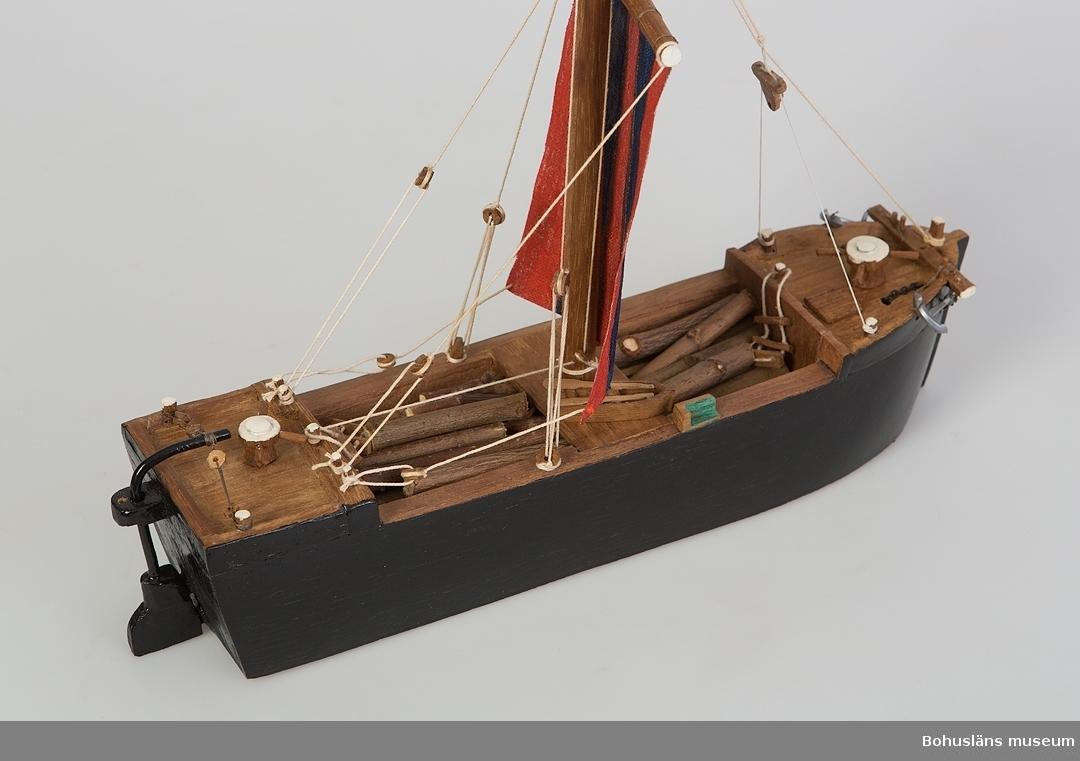 Modell av båttypen råbock i skala 1:100. Svartmålat träskrov med randigt  råsegel. Detaljer i metall och plast.