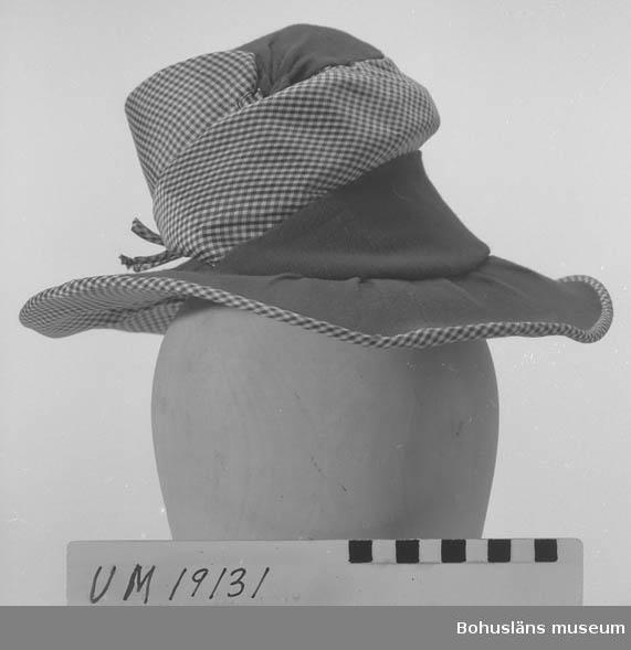 Föremålet visas i basutställningen Uddevalla genom tiderna, Bohusläns museum, Uddevalla.  410 Mått/Vikt ! BRÄTTB. 9 CM 394 Landskap BOHUSLÄN  Hatt i ljusbrunt tyg med rutigt foder och infällning på kullen. Rosett av tyget på kullens baksida.   Se UM19130.