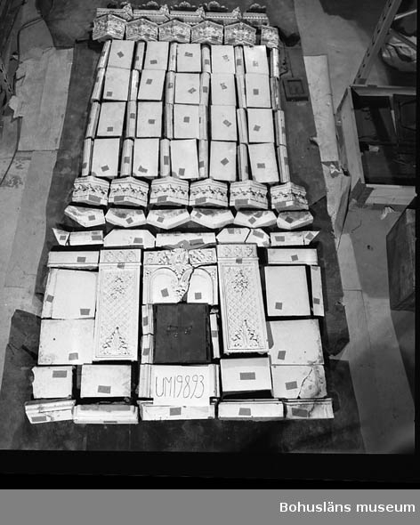 Vit kakelugn, femsidig med skulpterad övre sims, skänkband i form av hylla samt luckor av mässing (innerluckor saknas). 108 delar kakel, 1 spjäll, mässingsluckor med ram. Delarna märkta vid föremålsfotograferingen på 1980-talets andra hälft. Se bilaga.