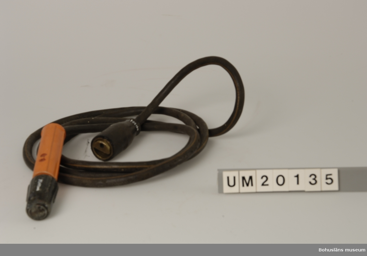 Föremålet visas i basutställningen Uddevalla genom tiderna, Bohusläns museum, Uddevalla.  410 Mått/Vikt ! DIAM 3,5,  DIAM 4 CM 594 Landskap BOHUSLÄN  Rött handtag och huvud med hål, en koppling för svetskabel.