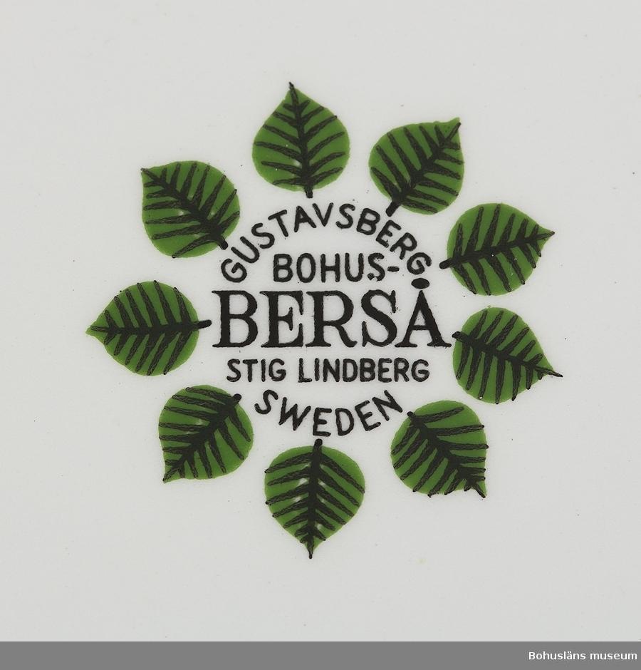 """Cylinderformad kopp. Dekor på kopp och fat av stiliserade gröna blad. Ur servis """"Berså"""". Formgivare: Stig Lindberg (1916 - 1982) och Krister Karlmark (född 1937).  Kopp H 60 x Diameter 86 mm Fat  H 20 x Diametere 157 mm"""