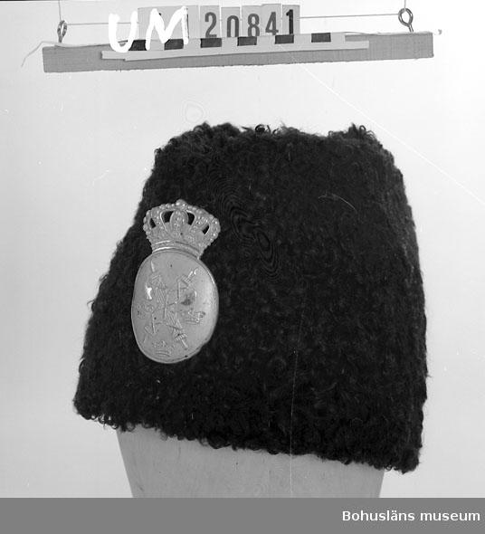 594 Landskap BOHUSLÄN 503 Kön MAN  Vintermössa för polis, helt i infärgat svart fårskinn, matlaserat ylle foder. Framtill ovalt märke med fascessknippen med yxor samt tre kronor. Ovanpå märket kunglig krona. Personuppgifter se UM 20831.