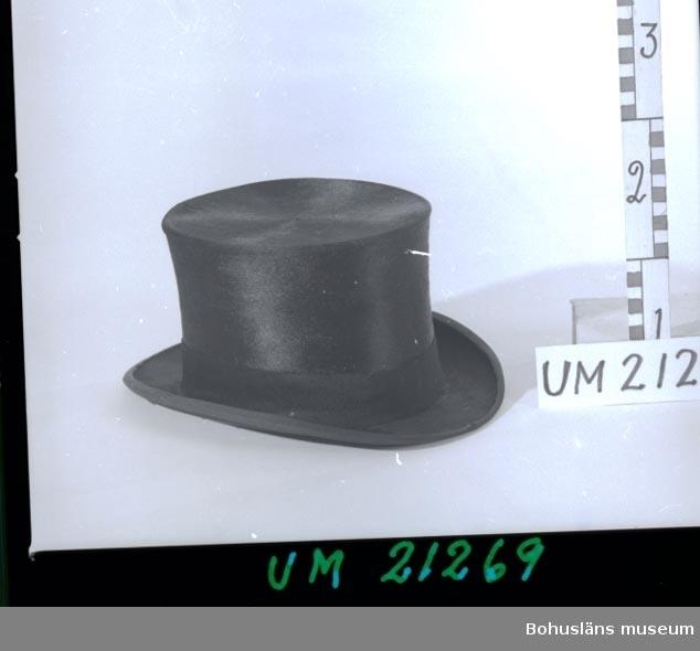 594 Landskap BOHUSLÄN  Hög hatt insvept i sjal UM21268 och förvarad i hattask UM21267. Läderbandet på hattens insida slitet p.g.a.användning. Insektsangreppskada på brättens undersida.  UMFF 6:6, 6:3