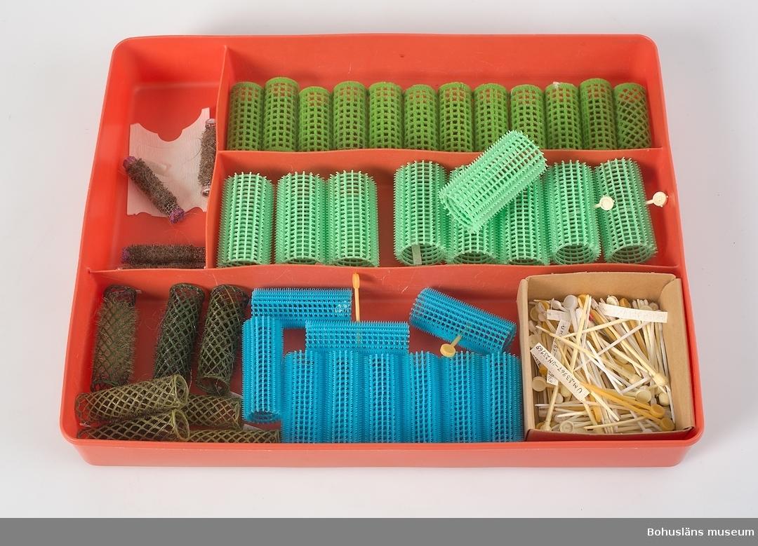 Låda av orange plast. I denna förvaras papiljotter och hårnålar UM023967 - UM023971  Föremål från Brorssons Damfrisering i Kungshamn, se UM023941