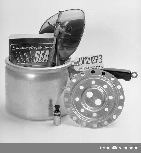 """Tryckkokare med dess tillbehör. Papperspåse med instruktioner. Inköpt 1941. Namn: FLEX-SEAL. Rund kastrull av aluminium. Böjligt lock av rostfritt stål. Handtag på kastrull och lock av bakelit. Locket spänns fast med en krok mellan handtagen. Pip mitt på locket som släpper ut övertryck i kastrullen. Ihop med pipen finns en manometer som anger tryck. På locket finns även en gummipropp med texten: """"Denna sida utåt"""". På lockets handtag hänger en folder: """"Vad Ni behöver veta om FLEX-SEAL TRYCKKOKARE"""". Brun papperspåse innehåller instruktionsskrifter (2 st, """"TRYCK-KOKARE gör arbetet lättare för husmor"""" och """"Instruktion för tryckkokaren FLEX-SEAL""""), en vikt att sätta på pipen och ett galler att lägga på."""