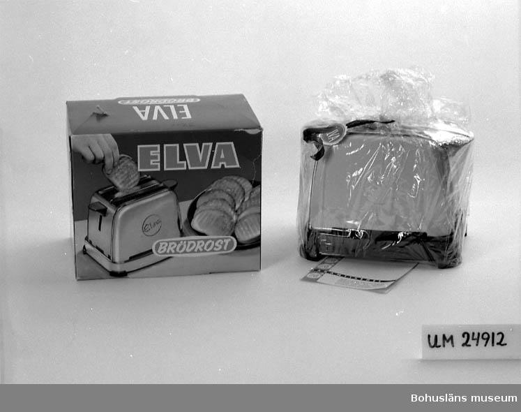 """Brödrost i originalförpackning. Brödrosten har gula långsidor. Nederdel och handtag är svart.  Ovansida och kortsidor är kromade. Är inslagen i cellofanpapper vilket är ihopbundet med ett vinrött band. Helt oanvänd. I lådan ligger dessutom en garantisedel med en bruksanvisning. Garantin är ifylld att gälla från den 6 september 1961. Enligt garantisedeln är brödrosten såld av Ernst Niklasssons Järnhandels AB.                                            På lådans lock står det: """"39.50"""" (handskrivet), """"ELVA BRÖDROST"""". På långsidorna är det ett fotografi av en brödrost som används - det ligger färdigrostade skivor bredvid och en hand tar upp en skiva ur rosten, text: """"ELVA BRÖDROST"""". På kortsidorna står det: """"BRÖDROST ELVA Nr 81302 GUL WATT 700 VOLT 220""""."""