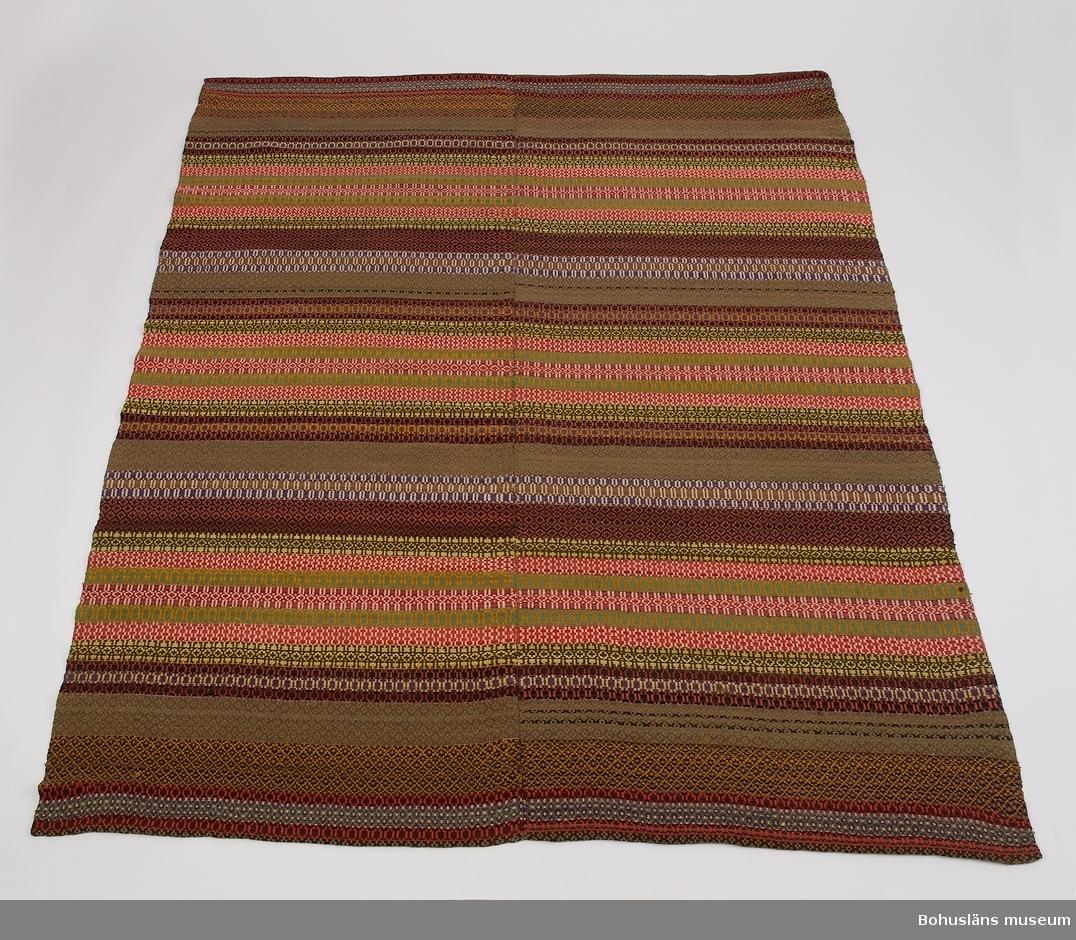 Handvävt täcke gjort i två våder, ihopsytt på mitten med längsgående söm. Med varp av lingarn och mönsterinslag av ullgarn. Småmönstrat i bunden rosengång solvad på 3 skaft. Mönstret består av smala bårder sammansatta till bredare partier, omväxlande ljusa och mörka. I de ca 35 cm breda mörka partierna är bårdernas bottenfärg grågrönt, svart, ljusbrunt och rödblått (lila) medan vitt, rödgult, ljusgrönt, ljusgult är mönsterfärger. De ljusa 18 cm breda partierna har bårder i rött/vitt, rött/vitt/rödblått (lila) och ljusgrönt/rödgult. Bland mönsterinslagen finns troligen både syntetfärgat och växtfärgat garn. Kortsidorna är fållade. Några stygn med blått och rött garn påsydda vid ena hörnet - en lagning? En liten svart fläck. För övrigt i gott skick.