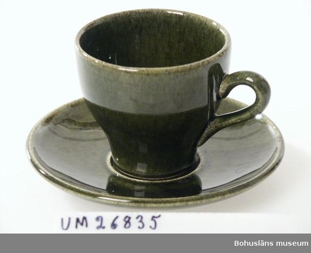 """410 Mått/Vikt KOPP: B 9,5 H 6,5 CM  FAT: DIAM 12 CM  Kaffekopp med fat. Av keramik glaserad i mörkt gröngult melerat medmycket mörkt brunt. Koppens form insvängd nertill, örats böj riktad snett uppåt. Mycket otydlig stämpel på undersidan. Hör samman med asssiett UM26836, gräddkanna UM26837 och sockerskål UM26838.  Föremålen är tillverkade av SYCO i Strömstad. Stämplingen är förmodligen """"NYA SYCO SWEDEN"""". De är inköpta på loppmarknad i Kviberg, Göteborg i januari 1999. Liknande kaffekanna fanns sedan tidigare i museets samling, se UM25117."""