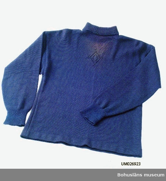 Tröja av blått tunt ullgarn. Slätstickad på stickmaskin med resårstickade ärmmuddar och krage gjorda för hand. Spetsstickat mönster fram upptill på bröstet: Lyfta och snodda maskor bildar hålmönster föreställande en romb med små romber i hörnen. (Rombmönster kan räknas som en traditionell bohuslänsk mönsterform. Vävda täcken på 1800-talet mönstrades ofta med romber.) Tröjan har rak kropp med (faststickad?) fåll nertill och polokrage upptill. Kragen är nervikt en gång mot rätan och fastsydd mitt fram, mitt bak och på axlarna. Tröjan har sidsömmar men inga axelsömmar, dvs tröjans bak och framstycke är gjorda i ett stycke med hål för halsen. Ärmarna är rakt isatta, förmodligen genom upplockade maskor i ärmhålet. Vida ärmhål, minskningar på ärmen på ett parti ca 18 cm ner från ärmhålet och ca 15 cm ovanför mudden, däremellan är ärmen rak. Mått ärmlängd 55 cm.