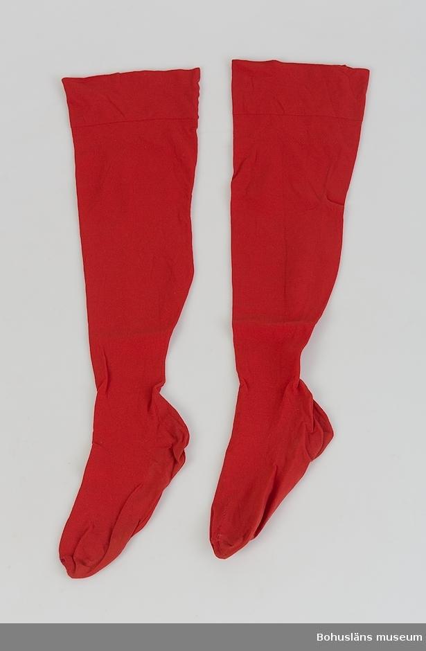 Ett par röda strumpor av silketrikå. Sammansydda  baktill från överkant till tån.  Något stoppade.